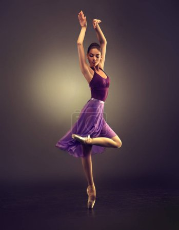 Ballerina. Young graceful woman ballet dancer, dressed in professional outfit, shoes and  weightless skirt is demonstrating dancing skill. Beauty of classic ballet.