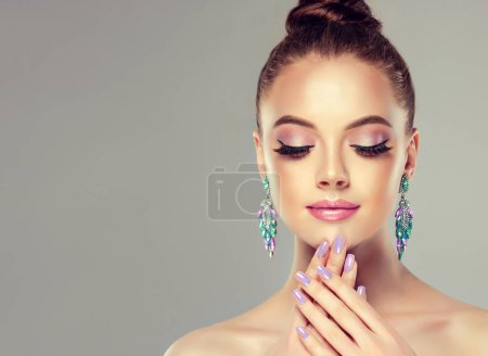 Beautiful model girl with manicure on nails . Fashion makeup and cosmetics . Large earrings tassels jewelry gray color .