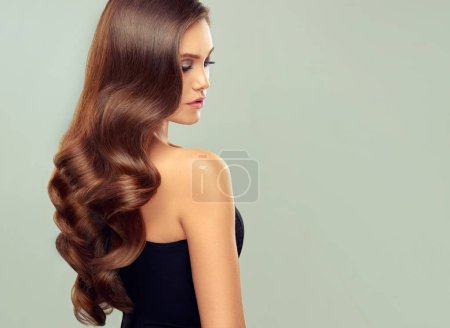 Photo for Brunette woman with long , healthy and shiny curly hair . - Royalty Free Image