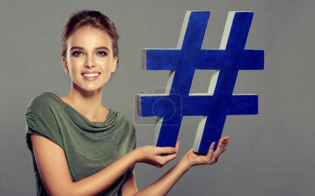 Photo for Smiling young woman holding hashtag sign in studio . social media concept - Royalty Free Image