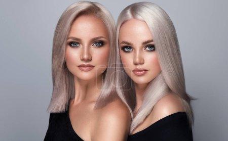 Photo pour Belles filles aux cheveux teints en blond. Boucles de coiffure élégantes faites dans un salon de beauté. Beauté, cosmétiques et maquillage - image libre de droit