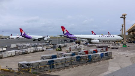 Photo for Honolulu, Hawaii - Aug 20, 2018 : Hawaiian Airlines planes on the ground and in the air at Honolulu International Airport in Hawaii - Royalty Free Image