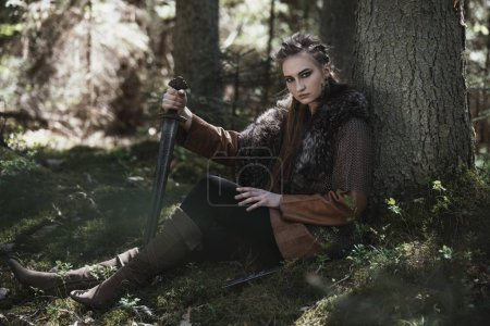 Photo for Viking woman with sword wearing traditional warrior clothes in a deep mysterious forest - Royalty Free Image