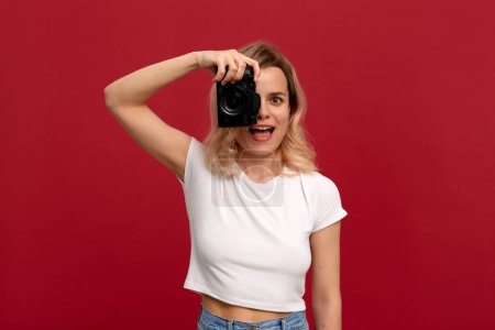 Photo for Portrait of a girl with curly blond hair dressed in a white t-shirt standing on a red background. Model takes photos with retro film camera. - Royalty Free Image