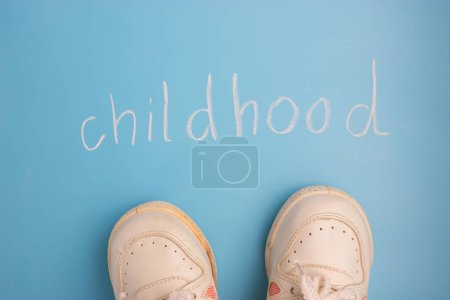 childhood concept. little sneakers on blue background
