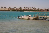 small boat near the wooden pier of the red sea and blue sky
