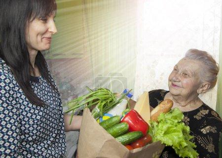 Photo pour Aide humanitaire à un pensionné de la travailleuse sociale; femme aider la vieille dame avec sa routine quotidienne; Le panier de produit pour le pensionné. - image libre de droit