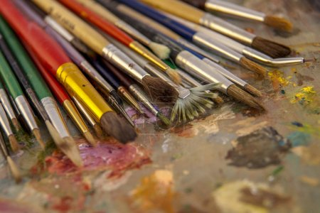 Photo pour An artist's brush on the palette, artists brushes and oil paints on wooden palette. - image libre de droit