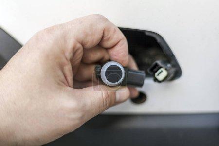 Photo pour Mécanicien de voiture change le capteur de stationnement sur la voiture, le dysfonctionnement du capteur de capteurs de stationnement - image libre de droit