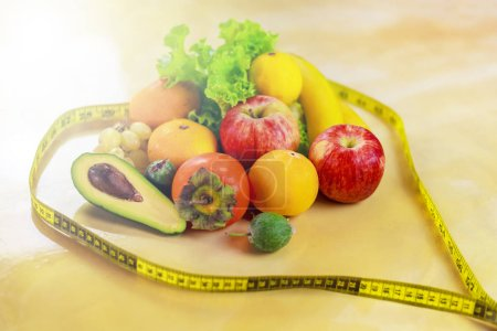 Photo for Concept of diet. Vegetables and fruits: Aavakado, figs, feijoa, cleansing the body, healthy eating, waist measuring tape - Royalty Free Image