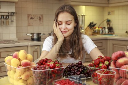 Beautiful young girl eats fruits and fresh berries in the kitchen, The girl dreamed of eating fruit, closed her eyes with pleasure