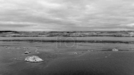 Foto en blanco y negro de una burbuja en la arena con un divorcio de las olas en el fondo del mar turbulento y el cielo nublado y lluvioso .
