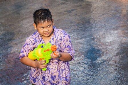 sukhothai, thailand - 15. April 2019: thailändische Kinder schießen mit Wasserpistole während des Neujahrssongkran water festivals