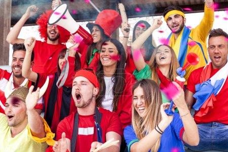 Foto de Grupo de aficionados vestidos de varios colores mirar un evento deportivo en las gradas de un estadio - Imagen libre de derechos