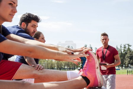 Photo for Group of athletes heats up the muscles before an obstacle course - Royalty Free Image