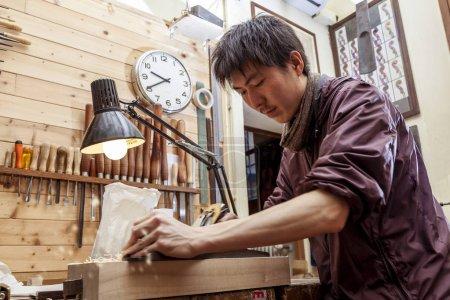 Photo for Craftsman japaneese violinmaker began working on a new violin in his workshop - Royalty Free Image