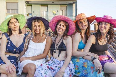 Photo pour Groupe d'amies en vacances assis sur les toits en bikini et paréo s'amuser au coucher du soleil concept de fêtes et de vacances - image libre de droit