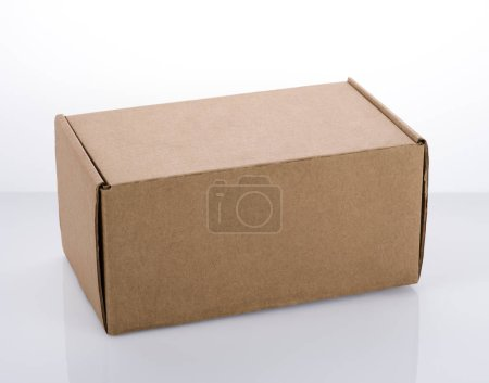 A small cardboard box on a white table. Free space on the surface