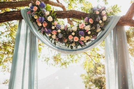 Photo pour Cérémonie de mariage au coucher du soleil, arche décorée d'un tissu gris accroché à un grand arbre et à des fleurs roses - image libre de droit