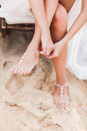 Woman wearing adornment on feet, standing on sandy beach, wedding day, brides style