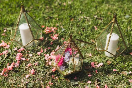Photo pour Mariage décorations de cérémonie avec beaucoup de bougies à l'intérieur de boîtes en verre transparent de cône à la main. Autour des pétales de fleurs en herbe - image libre de droit