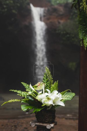 Wedding bouquet of tropical flowers and leaves with waterfall on background