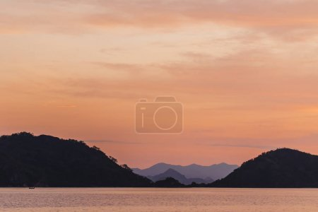 Photo for Orange background with black and blue mountain silhouettes on horizon. Sunset tropical landscape - Royalty Free Image