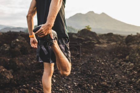 Photo for Runner stretching leg and feet and preparing for trail running outdoors. Active and healthy lifestyle concept. Mountain view on background. - Royalty Free Image