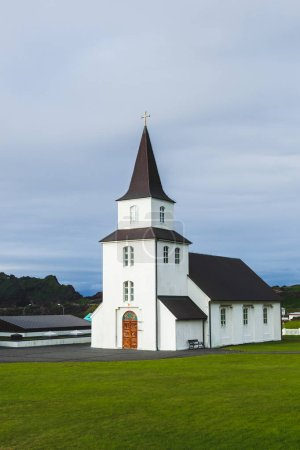 Photo pour Eglise avec toit noir et murs blancs dans le style minimaliste nordique traditionnel sur l'île de Vestmannaeyjar Heimaey en Islande. Architecture simple, herbe verte, personne autour . - image libre de droit