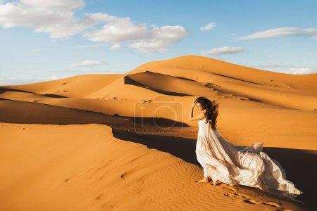 Photo pour Femme en robe de mariée en soie étonnante avec vue fantastique sur les dunes de sable du désert du Sahara à la lumière du coucher du soleil. Paysage du Maroc, Afrique . - image libre de droit