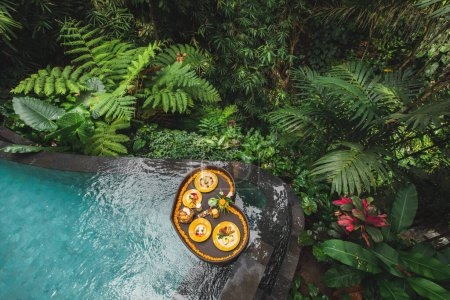 Photo for Floating breakfast in jungle swimming pool, tropical resort. Black rattan tray in heart shape, Valentines day or honeymoon surprise, view from above. Exotic summer diet. Tropical beach lifestyle. - Royalty Free Image