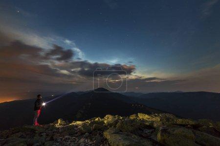 Photo pour Belle nuit d'été en montagne. Profil silhouette de jeune randonneur touristique homme avec lampe de poche debout seul sur le sommet des montagnes rocheuses sous ciel bleu foncé nuageux étoilé au coucher du soleil. Concept de tourisme . - image libre de droit