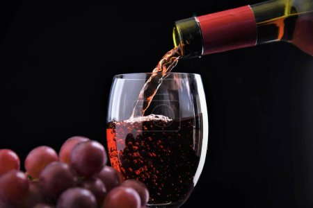 Photo for Red wine glass with grape and bottle pouring - Royalty Free Image