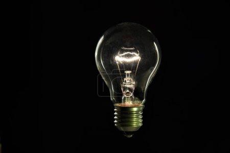 Photo pour Ampoule incandescente sur fond noir - image libre de droit