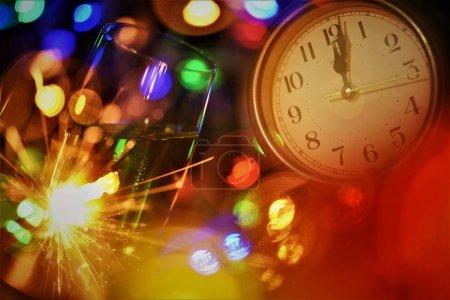 Photo pour Nouveau symbole de célébration de l'année ; verre de champagne feu d'artifice couleur lumière et horloge visage à une minute après minuit - image libre de droit