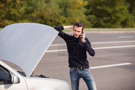 Photo pour Homme appelant par téléphone pour obtenir de l'aide avec sa voiture endommagée - image libre de droit