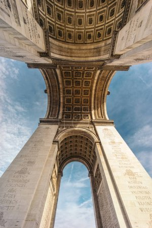 The Arc de Triomphe de l'Etoile (Triumphal Arch of the Star) is one of the most famous monuments in Paris, standing at the western end of the Champs-Elyseees