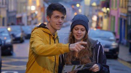 Photo pour Jeune couple une excursion cherche des directions sur une carte - image libre de droit