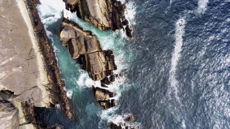 Photo for Aerial view over blue ocean water and the rocky coast if Ireland - Royalty Free Image