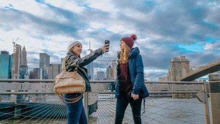 Photo pour Deux jeunes femmes à New York à pied le long de la ligne d'horizon typique au pont de Brooklyn - photographie de voyage - image libre de droit
