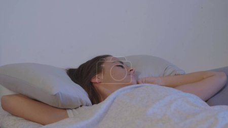 Photo pour Jeune femme dans son lit se réveille tôt le matin - image libre de droit
