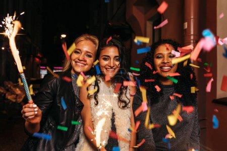 Foto de Grupo de amigos con luces de Bengala disfrutando de fin de año en confeti - Imagen libre de derechos