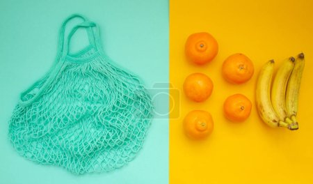Photo for Tangerines and oranges lie in a neo mint string bag - Royalty Free Image