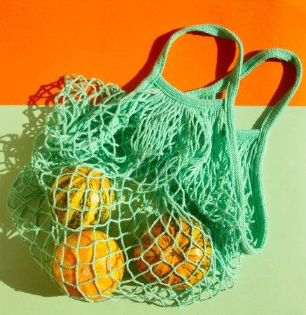 Photo pour Petites citrouilles d'automne décoratives dans un sac à ficelle verte. Légumes dans un sac à provisions sur fond vert. - image libre de droit