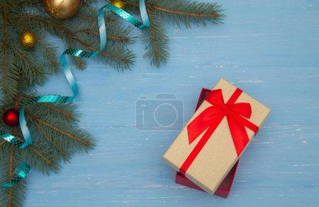 Photo pour Belle boîte cadeau sur un fond bleu en bois. branches d'arbre de Noël sur la table. Bonne année ! - image libre de droit