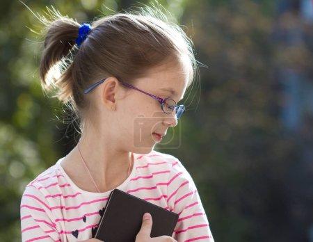 Photo pour Portrait d'une jolie petite fille en lunettes avec livre - image libre de droit