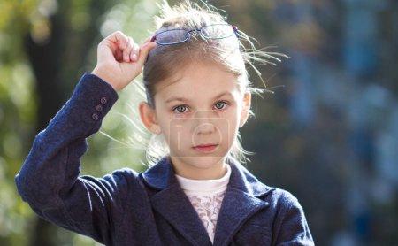 Photo pour Portrait d'une jolie petite fille en lunettes - image libre de droit