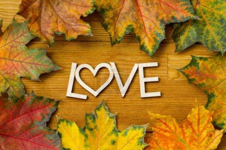 Photo pour Inscription en bois AMOUR sur une feuille d'automne sur une table rurale en bois. Tourné d'en haut. - image libre de droit