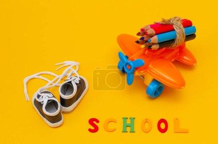 Photo pour Crayons de couleur sur un petit jouet avion orange sur fond jaune. - image libre de droit