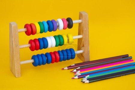 Photo pour Abaque scolaire pour enfants et crayons en bois de couleur sur fond jaune. - image libre de droit
